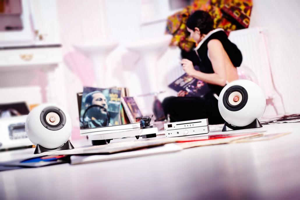 Eine Frau sitz am Boden und hört Platten mit Augarten Lautsprechern und einem Plattenspieler von Pro-ject, MaiA Verstärker und CD Box S.