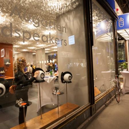 Eine Frau streichelt sanft über den Augarten Lautsprecher von mo° sound. In dem Augarten Flagship Store Wien.