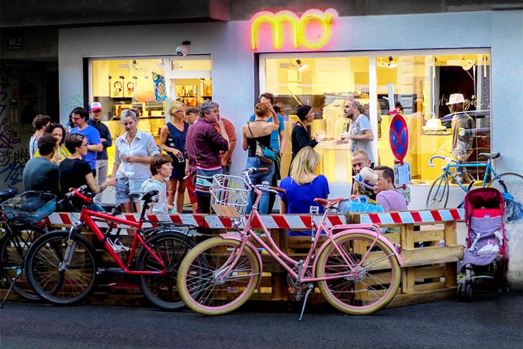 mo° sound store, Kirchengasse 40, 1070 Wien. Menschen die im Sommer vor dem Lokal sitzen und stehen.