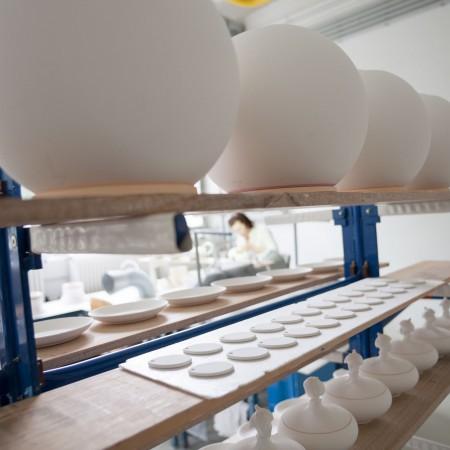 Gehäuse Rohlinge in der Augarten Manufaktur Wien. Handwerkerin die im Hintergrund arbeitet.
