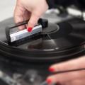 Eine Frauenhand reingt eine Platte mit einem Carbonfaser-Bürstchen im mo° sound store in Wien.