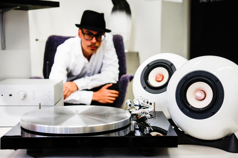 Plattespieler von Pro-Ject Audio und Verstärker, Kugellautsprecher aus Augarten Porzellan, dahinter Mann mit Hut der Musik hört.