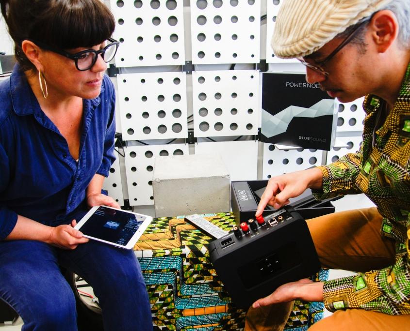 Eine Frau und ein Mann schauen einen Streaming Verstärker an im mo° sound store