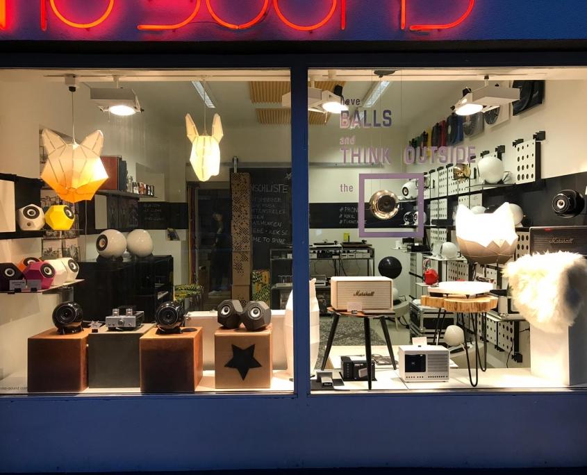 Front des mo° sound stores und zahlreiche Produkte in der Auslage bei Nacht mit Neonschrift - mo° sound