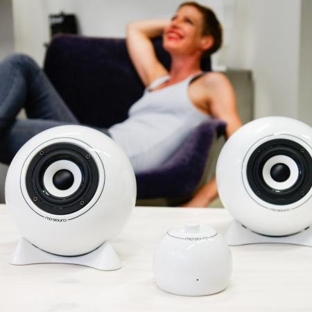 Kugellautsprecher aus Porzellan und Kugel-Verstärker aus Porzellan und Frau die sich freut im Hintergrund